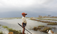 A boy whose house was destroyed by Cyclone Nargis that hit Myanmar in May 2008 watches an approaching storm. [Photo: UNICEF/Adam Dean]